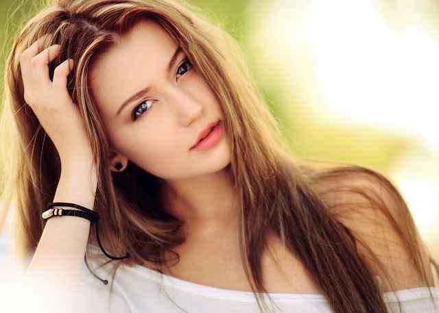 красива млада жена гледа съблазнтелно и тя флиртува като си докосва косата