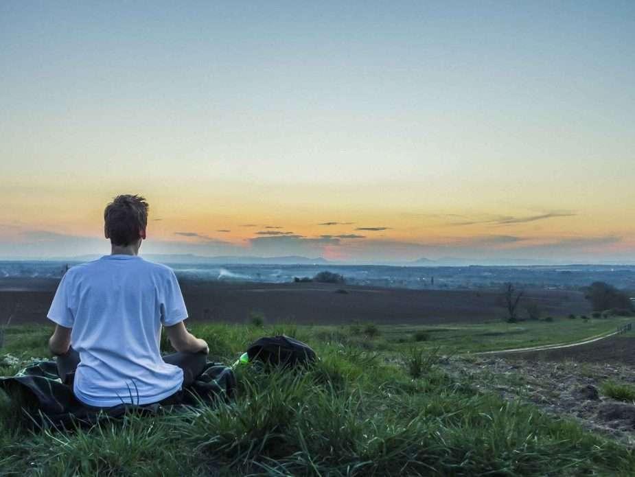 мъж медитира сред природата